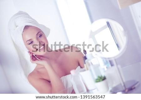 Young woman in bathrobe looking in bathroom mirror #1391563547