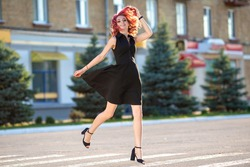 young woman in beautiful black dress running crosswalk on sunny summer day