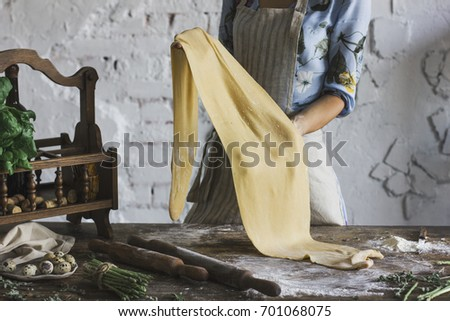 Young woman in beautiful dress and apron preparing the dough for homemade pasta #701068075