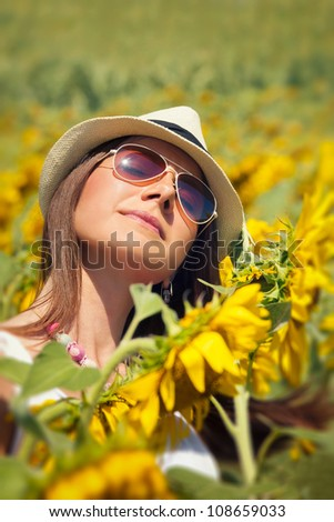 Young woman in beauty field with sunflowers