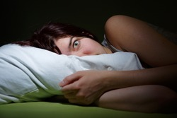 Young woman in bed  eyes opened suffering insomnia. Nightmare issues