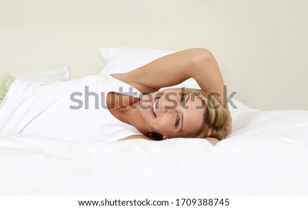 Young woman in bed smiling