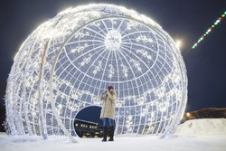 Young woman in big glowing christmas tree ball. She congratulating friends happy new year by phone.