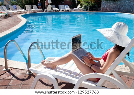 Young woman in big hat relaxing near the pool with laptop