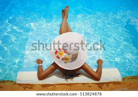 young woman in big white hat rested on a lounger in the pool stock photo
