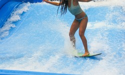 Young woman in bikini and tank top surfing on wave pool with small board in the island of Phuket, Thailand