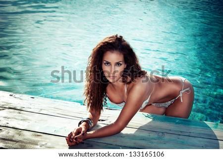 young woman in bikini in the pool outdoor shot summer day