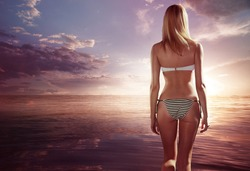 Young woman in bikini standing and looking on sunset