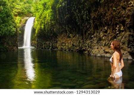 Young woman in bikini standing at Wainibau Waterfall on Taveuni Island, Fiji. Taveuni is the third largest island in Fiji.