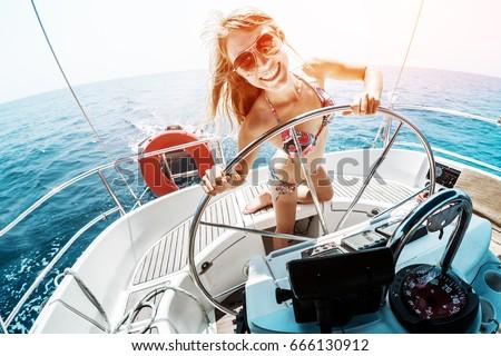 Young woman in bikini steering the sailing boat in a tropical sea