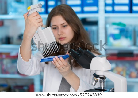 Young woman in biological laboratory. Attractive young female scientis.Young scientist pipetting with multi pipette in genetic lab.
