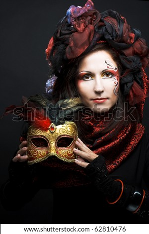 Young woman in black and red silk with mask in her hands