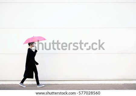 Stock Photo Young woman in black clothes walking with pink umbrella