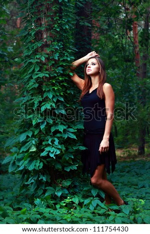 Young woman in black dress at fairy green forest