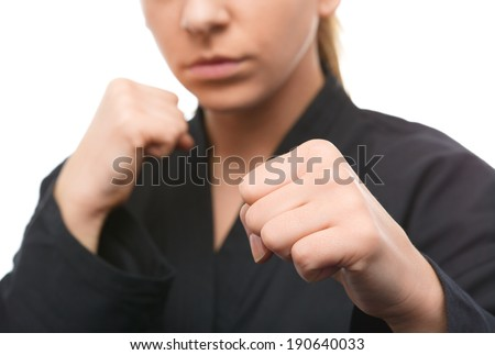 Young woman in black kimono is ready to fight, isolated over white