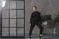 Young woman in black sportswear, pants and sweatshirt. Concept of fashionable sport outfit, indoors photo. Copy space.
