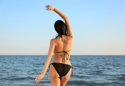 Young woman in black stylish bikini on beach, back view