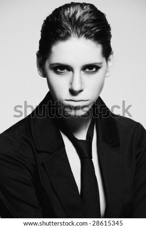 young woman in black vest black tie androgyn looks