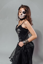 Young woman in black with half face skull make-up.