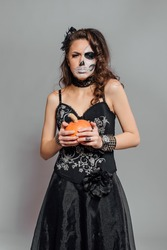 Young woman in black with half face skull make-up and pumpkin in hand.
