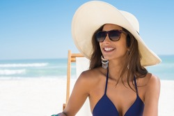 Young woman in blue bikini sitting on deck chair wearing white straw hat. Happy girl enjoying summer vacation at beach. Portrait of beautiful latin woman relaxing at beach with sunglasses.