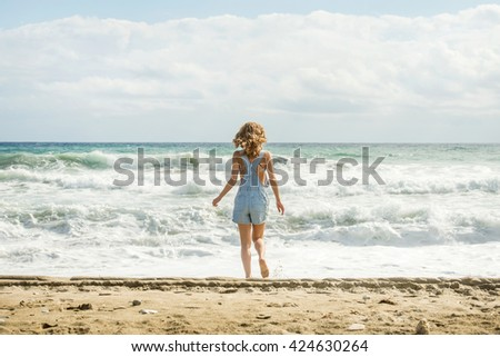 8ff2cc86f754 Young woman in blue denim jumpsuit walking towards stormy sea  424630264