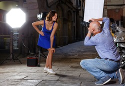 young woman in blue dress posing for professional photographer on old city street