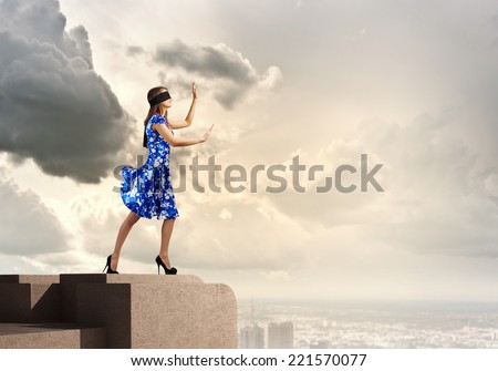 Young woman in blue dress standing on roof edge #221570077