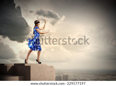 Young woman in blue dress standing on roof edge #229577197