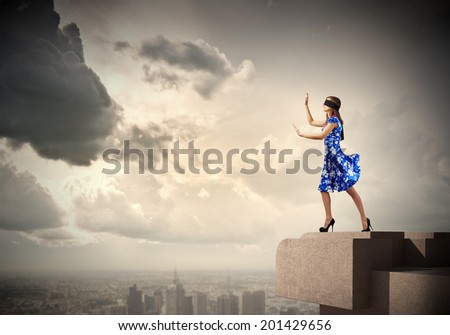 Young woman in blue dress walking on edge of roof #201429656