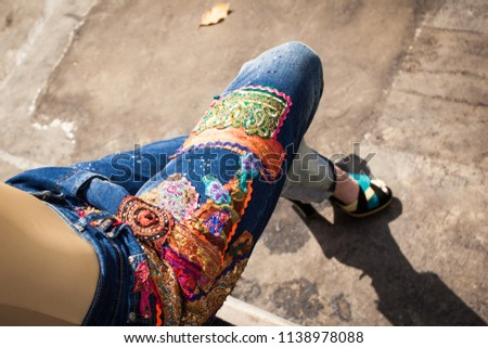 young woman in blue embroidered  jeans and high heels in backyard summer fashion closeup from above view