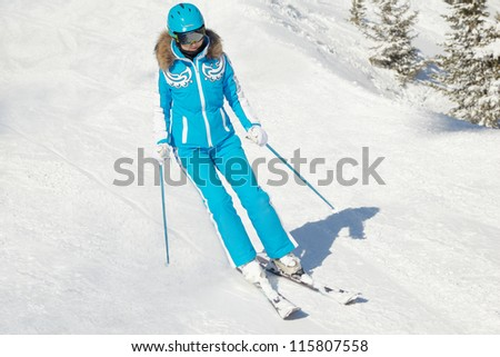 Young woman in blue ski suit and blue helmet skis in bright winter day