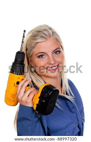 young woman in blue work clothes with a drill.