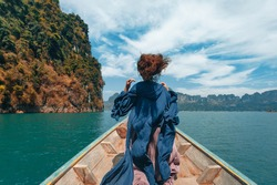young woman in boho style dress on boat at the lake