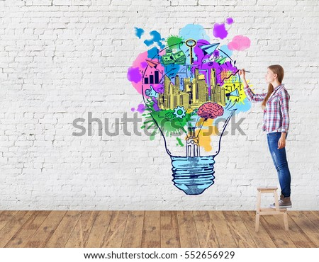 Young woman in brick room drawing creative light bulb. Business ideas concept