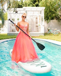 Young woman in bright pink prom dress unexpectedly paddle boarding in a backyard swimming pool with garden structure and beach cruiser in the background