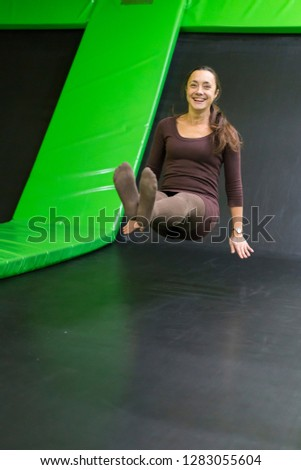 young woman in brown fit dress on trampoline in trampoline center. vertical photo. Happy girl on trampoline. vertical photo.