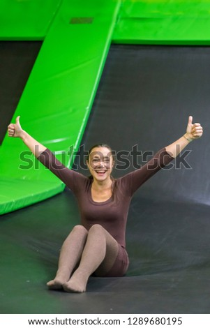 young woman in brown fit dress on trampoline in trampoline center. vertical photo. Happy girl on trampoline. Happy young woman on trampoline. vertical photo.