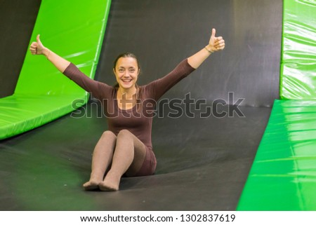 young woman in brown fit dress on trampoline in trampoline center. vertical photo. Happy girl on trampoline. Happy young woman on trampoline.