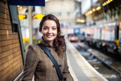 Young woman in brown winter coat waiting on train station