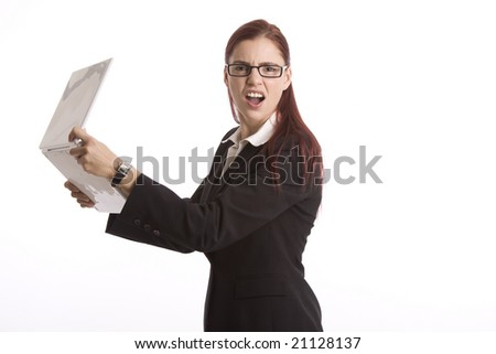 Young woman in business attire angrily holding a laptop computer