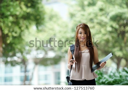 Young woman in business attire, carrying briefcase and holding folder standing outside.