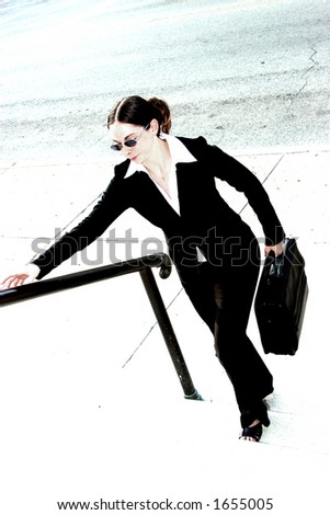 Young woman in business attire, carrying briefcase and walking up some steps.