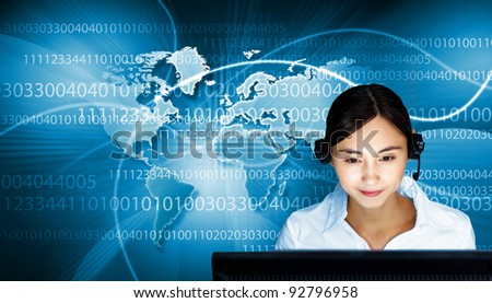 Young woman in business wear in headset working with computer