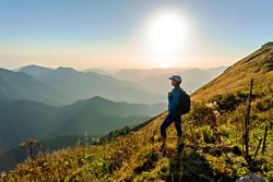young woman in cap with backpack standing among Caucasus mountains and looking at setting sun and mountain view. Landscape, Aibga ridge, hiking, travel alone, beauty in nature,  World Tourism Day