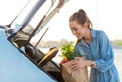 Young woman in car park, loading shopping into boot of car