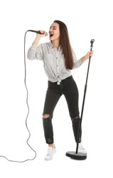 Young woman in casual clothes singing with microphone on white background