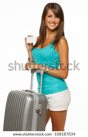 Young woman in casual standing with silver travel suitcase holding empty credit card, isolated on white background