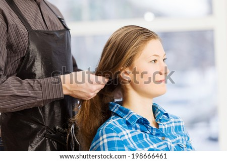 Young woman in chair at barbers and male hairdresser
