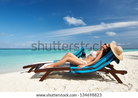 Young woman in chaise lounge at the beach